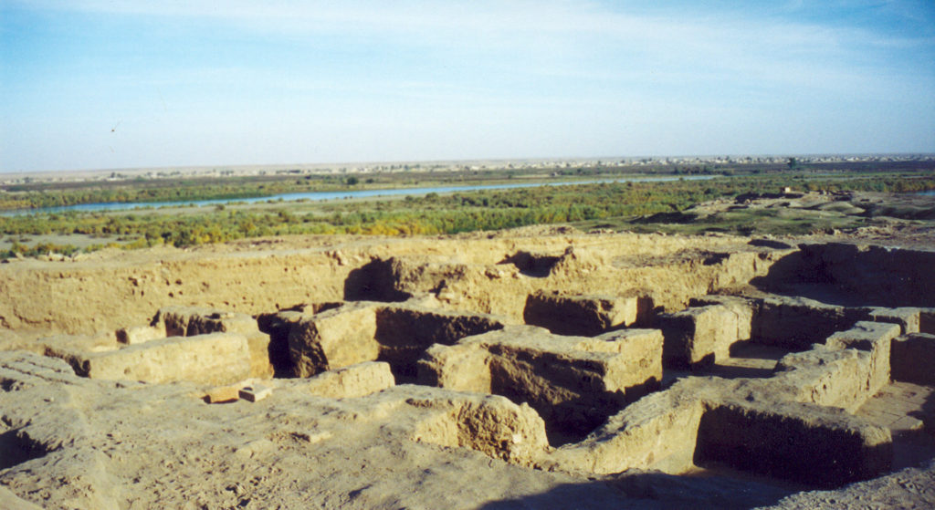 image illustrating the archaeological ruins of ashur in iraq. mudbrick remains of a building appear in the foreground. the river tigris appears in the background