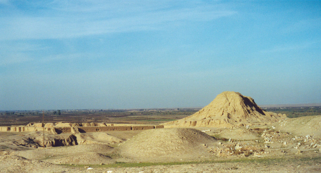image illustrating the archaeological site of ashur in Iraq. a high mound appears to the right, with other mudbrick remains in the foreground and left