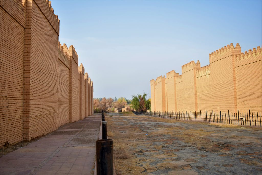 image illustrating the reconstructed processional way at the archaeological site of babylon in iraq. brick walls in neo-babylonian style appear on each side of a paved way