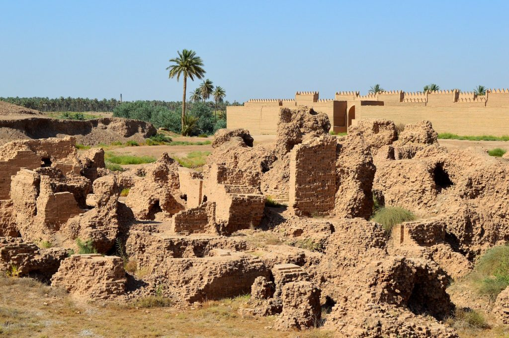 image illustrating the archaeological ruins of babylon in Iraq. remains of brick structures appear in the foreground and reconstructed brick walls appear in the background